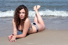 Teenage girl on beach. Pretty teenage girl lying on stomach on beach Royalty Free Stock Images