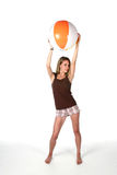 Teenage girl with beach ball up high Stock Image