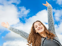 Teenage Girl. With beautiful long curly hair, arms up in the air, she looks very happy Royalty Free Stock Photography