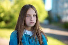 Teenage girl with beautiful long hair. Freckles on the face. Poses on the camera stares. In the summer in the park in royalty free stock photography