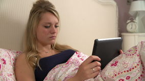 Teenage Girl In Bed Using Tablet Computer Being Bullied