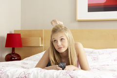 Teenage Girl In Bedroom With Mobile Phone Stock Image