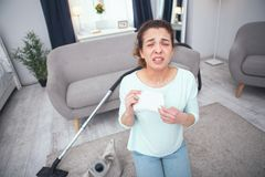 Teenage girl being allergic to dust while vacuum cleaning the carpet. Household chores. Teenager girl holding a paper tissue looking unwell and failing to cope Royalty Free Stock Photos