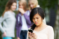Teenage Girl Being Bullied By Text Message On Mobile Phone. Upset Teenage Girl Being Bullied By Text Message On Mobile Phone royalty free stock image