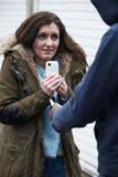 Teenage Girl Being Mugged For Mobile Phone. Teenage Girl Getting Mugged For Mobile Phone royalty free stock image