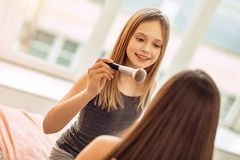 Teenage girl being about to apply makeup to sisters face. Makeup training. Cute teenage girl sitting on the bed in front of her elder sister and being about to Stock Photo