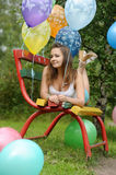 Teenage girl on a bench with balloons Stock Photography