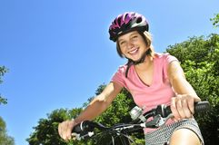 Teenage girl on a bicycle. Portrait of a teenage girl on a bicycle in summer park outdoors royalty free stock photography