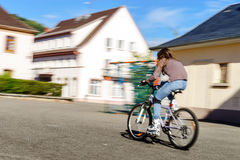 Teenage girl bicycling in roller boots. Speed shooting. Teenage girl bicycling in roller boots. Quickly moving Stock Image