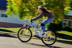 Teenage girl bicycling in roller boots. Speed shooting Royalty Free Stock Photos