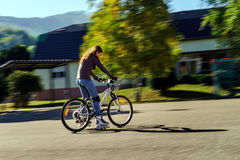 Teenage girl bicycling in roller boots. Speed shooting. Teenage girl bicycling in roller boots. Quickly moving Royalty Free Stock Photography