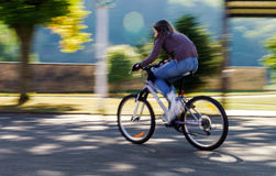 Teenage girl bicycling in roller boots. Speed shooting. Teenage girl bicycling in roller boots. Quickly moving Stock Images