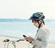 Teenage girl with bike listening to music on her phone. Royalty Free Stock Photos