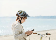 Teenage girl with bike listening to music on her phone. Royalty Free Stock Photography