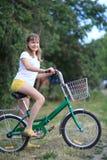 Teenage girl with a bike-riding. A teenage girl with a bike-riding in the street stock image
