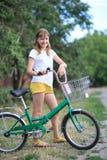 Teenage girl with a bike-riding. A teenage girl with a bike-riding in the street royalty free stock photo