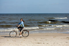 Teenage girl biking on beach Royalty Free Stock Image
