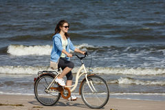 Teenage girl biking on beach Stock Photos
