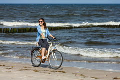 Teenage girl biking on beach Stock Images