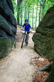 Teenage girl biking on forest trails Royalty Free Stock Photo