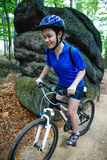 Teenage girl biking on forest trails Stock Photos