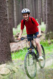 Teenage girl biking on forest trails Royalty Free Stock Image
