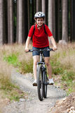 Teenage girl biking on forest trails Royalty Free Stock Image