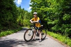 Teenage girl biking on forest trails Stock Photo