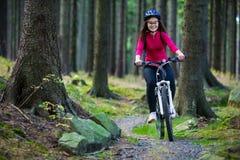 Teenage girl biking on forest trails Royalty Free Stock Photo