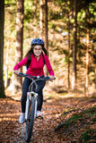 Teenage girl biking on forest trails Stock Images