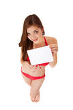 Teenage girl in bikini holding blank white card Stock Photography