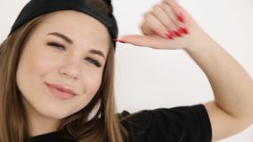 A teenage girl in black hip-hop clothes and a cap dances at the white wall- close-up, handheld shoot, small depth of. Field stock video