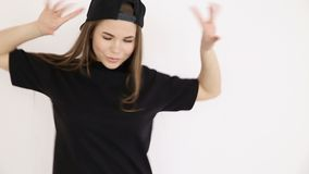 A teenage girl in black hip-hop clothes and a cap dances at the white wall- close-up, handheld shoot, small depth of. Field stock video footage