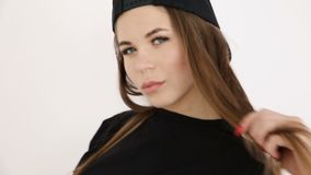A teenage girl in black hip-hop clothes and a cap dances at the white wall- close-up, handheld shoot, small depth of. Field stock footage