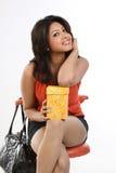 Teenage girl with  black leather bag. Teenage girl sitting on chair black leather bag and gift box Stock Image