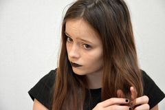 Girl with black painted lips  plaits her hair Stock Images