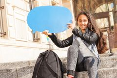 Teenage girl with blanked blue speech bubble. Smiling beautiful teenage girl sitting on the stairs outdoors, holding blanked blue speech bubble Royalty Free Stock Photos