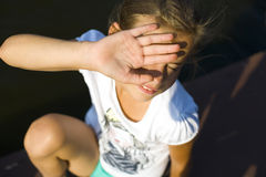 Teenage girl blinks from the sun. In midday heat stock photos