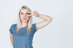 Teenage girl with blond hair showing peace sign Stock Images
