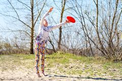 Teenage girl, blonde catches flying disk in a jump Royalty Free Stock Photography