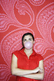 Teenage Girl Blowing Bubble Against Wallpaper Royalty Free Stock Images