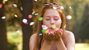 Teenage girl blowing confetti off hands in park stock video footage