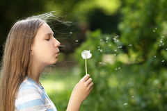 Teenage girl blowing a dandelion Royalty Free Stock Photo