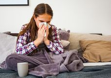 Teenage girl is blowing her nose while sitting on a sofa. Headache. Virus. Medicines Stock Photos