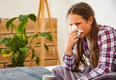 Teenage girl is blowing her nose while sitting on a sofa. Headache. Virus. Medicines Stock Image