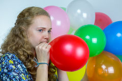 Teenage girl blowing inflating colored balloons Royalty Free Stock Photography