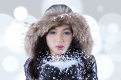 Teenage girl blowing snow with bokeh background. Picture of attractive teenage girl blowing snow on her palms while wearing winter jacket with bokeh background Stock Photo
