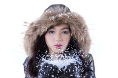 Teenage girl blowing snow in studio. Picture of beautiful girl wearing winter jacket and blowing snow on her hands in the studio, isolated on white background Royalty Free Stock Photos