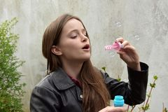 Teenage girl blowing soap bubbles. Cute teenage girl with long brown hair blowing soap bubbles royalty free stock photo