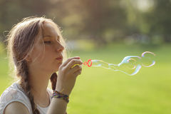 Teenage girl blows soap babbles in te park Royalty Free Stock Photos